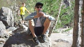 Kerltrieb am Telefon, sitzt auf einem Stein stock footage