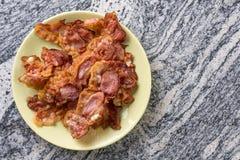 Kernachtig gebraden bacon op de plaat boven grijze granietlijst als achtergrond stock afbeelding