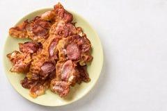 Kernachtig gebraden bacon op de plaat boven witte marmeren lijst als achtergrond stock fotografie