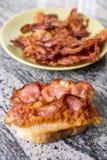 Kernachtig gebraden bacon op het brood boven grijze granietachtergrond stock fotografie