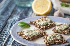Kernachtig korrelbrood met tzatziki op de blauwe ceramische horizontale plaat stock foto