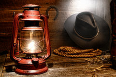 Kerosene Lamp in American West Rodeo Cowboy Barn. Vintage kerosene lantern lamp illuminating American West rodeo cowboy gear with hat and ranching lasso rope royalty free stock photography