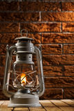 Kerosene lamp on brick background Royalty Free Stock Photography