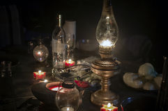 Kerosene Lamp And Food. A kerosene lamp in focus and candles around the table with some food and drinks left, night scene, concept of blackout Stock Photo