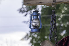 Kerosene lamp. Metal blue old kerosene lamp with blacksmith chain Stock Photography