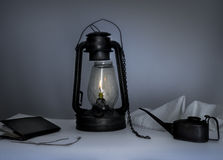 Kerosene lamp, oiler, a notebook on  table in the twilight Royalty Free Stock Photography