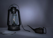 Kerosene lamp, oiler, a notebook on  table in the twilight Stock Photo