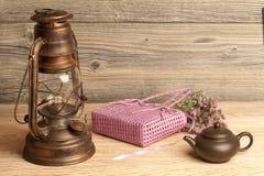 Kerosene lamp, tea pot, flowers and bag on wood Royalty Free Stock Image