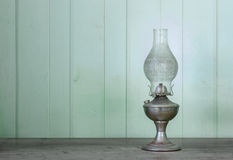 Kerosene lamp on wooden table and antique wooden wall Royalty Free Stock Image