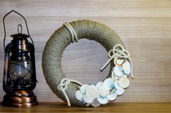 Kerosene lamp and a wreath in a nautical theme. Still life in a marine style. Home decor wreath of rope with shells. Decorating knot Stock Photos