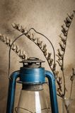 Kerosene lantern and a dry branch of bleached on the background of the plastered wall. Still-life in the rustic style royalty free stock photo