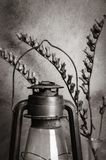 Kerosene lantern and a dry branch of bleached on the background of the plastered wall. Still-life in rustic style, monochrome royalty free stock images