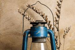 Kerosene lantern and dry branch of bleached. Still-life in the rustic style stock image