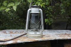 Kerosene oil lamp on roofing slate and apple tree. Close up Stock Photography