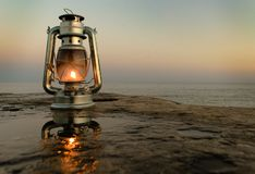 Kerosene vintage lamp on the pier by the sea in the evening. stock image