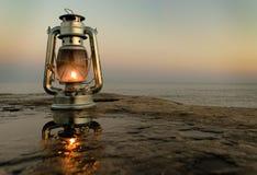 Kerosinweinleselampe auf dem Pier durch das Meer am Abend stockbild