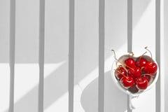 Kersen Chili in hart-Vormige mok op hout Royalty-vrije Stock Afbeeldingen