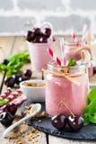 Kersen gezonde smoothie met granola en bessen Stock Foto's