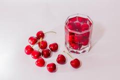 Kersen in glas en een handvol kersen naast Royalty-vrije Stock Foto
