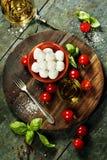 Kersentomaten, basilicumbladeren, mozarellakaas en olijfolie F Stock Foto