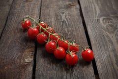 Kersentomaten, een bos van rode rijpe tomaten op een houten achtergrond stock foto