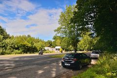 Kersko,捷克共和国- 2018年7月07日:路与导致在树之间的两辆摩托车的第611有停放的汽车的Sadska镇 免版税图库摄影