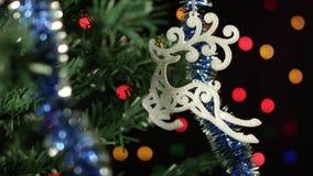 Kerstboom die, Kerstmisstuk speelgoed herten op een achtergrond van vage lichten verfraaien stock video