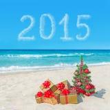 Kerstboom en giftdozen op overzees strand Concept voor nieuw jaar Stock Afbeeldingen