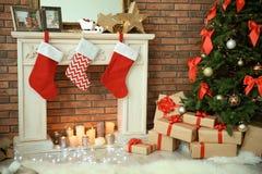 Kerstboom en giften dichtbij decoratieve open haard met kousen binnen stock foto's