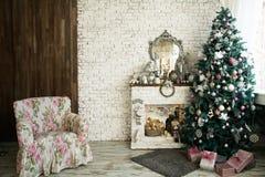 Kerstboom en open haard met een leunstoel stock afbeeldingen