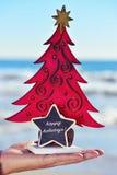 Kerstboom en tekst gelukkige vakantie op het strand Royalty-vrije Stock Afbeeldingen
