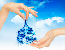 Kerstboom in handen op een blauwe hemel Royalty-vrije Stock Afbeeldingen