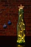 Kerstboom met een slinger als groene fles op de achtergrondmuur Stock Afbeeldingen