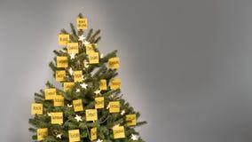Kerstboom met 25 gele post-itnota's wordt verfraaid met bedrijfssleutelwoorden en wensen die royalty-vrije stock afbeeldingen