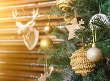 Kerstboom met gouden ballen, decoratie Herten hoofdmodel op de muur Het concept van het nieuwjaar Gestemde zon glanzende sinaasap stock foto