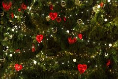 Kerstboom met heards en lichten wordt verfraaid dat Stock Afbeeldingen
