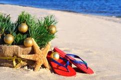 Kerstboom met Kerstmisballen, pantoffels en zeester op Th Stock Foto's