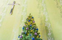 Kerstboom met klatergoud en ballen en het kruis Stock Foto