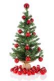 Kerstboom met rode die ballen wordt bij wit worden geïsoleerd verfraaid dat Stock Foto