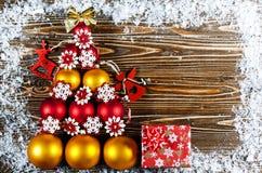 Kerstboom, met rode en gouden Kerstboomballen die wordt gevoerd Het kerstboomspeelgoed ligt op een houten oppervlakte Royalty-vrije Stock Foto's