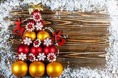 Kerstboom, met rode en gouden Kerstboomballen die wordt gevoerd Het kerstboomspeelgoed ligt op een houten oppervlakte Naast de bo Stock Foto