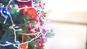 Kerstboom met slingers en speelgoed wordt verfraaid dat stock footage