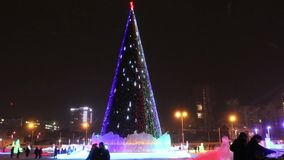 Kerstboom met verlichting en lopende mensen die in de winter, Permanent, Rusland gelijk maken stock footage