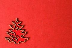 Kerstboom op de rode achtergrond van de textuur, houten ecodecoratie, stuk speelgoed Stock Foto