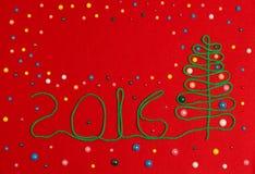 2016 Kerstboom op gevoeld rood Stock Foto
