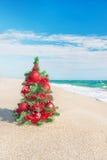 Kerstboom op het overzeese strand Het concept van de Kerstmisvakantie Stock Foto
