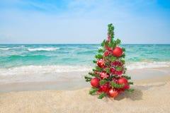 Kerstboom op het overzeese strand Het concept van de Kerstmisvakantie Stock Fotografie