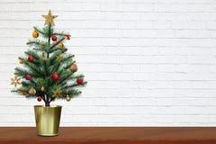 Kerstboom op houten lijst met exemplaarruimte op witte bakstenen muurachtergrond royalty-vrije stock foto's