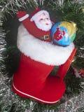 Kerstboom Toy Santa Claus met een grondbal en een geboorte van Christus Saphok tegen de achtergrond van een kunstmatige Kerstboom royalty-vrije stock foto
