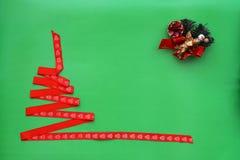 Kerstboom van rood lint, buil, engel op groene achtergrond wordt gemaakt die Het concept van Kerstmis en van het Nieuwjaar stock fotografie